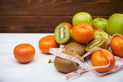 Tropical fruits and apples with measuring tape, Royalty Free Stock Images