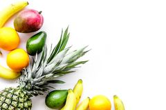 Tropical fruits background. Mango near exotic leaf, banana, oranges and pineapple on white top view copyspace Royalty Free Stock Photography