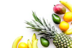Tropical fruits background. Mango near exotic leaf, banana, oranges and pineapple on white top view copyspace Royalty Free Stock Photo