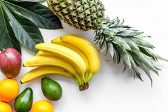 Tropical fruits background. Mango near exotic leaf, banana and pineapple on white top view copyspace Royalty Free Stock Photo