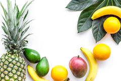 Tropical fruits background. Mango near exotic leaf, banana, oranges and pineapple on white top view copyspace Stock Photo
