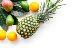 Tropical fruits background. Mango near exotic leaf and pineapple on white top view copyspace Stock Photo