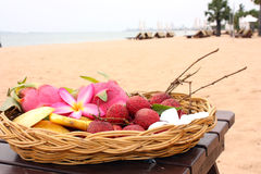 Tropical fruits on the beach. Basket with a tropical fruits on the beach Stock Photos