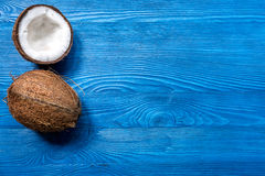 Tropical fruits with broken coconut on blue wooden background top view space for text Royalty Free Stock Image