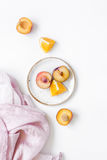 Tropical fruits design with orange and peach on fabric white table background top view Royalty Free Stock Photos