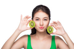 Tropical fruits. Healthy eating. Charming young asian woman hold. Ing fresh juicy kiwi and smiles. Green background Royalty Free Stock Images