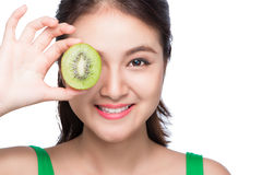 Tropical fruits. Healthy eating. Charming young asian woman hold. Ing fresh juicy kiwi and smiles. Green background Royalty Free Stock Photo