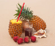 Tropical fruits with juice on the sandy beach. Stock Photography
