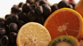Tropical fruits on a plate. Tropical fruit mix with grapes stock footage