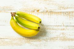 Tropical fruits ripe yellow greenish bananas on white planked wood table. Healthy diet vitamins breakfast fiber source concept. Poster banner template. Flat stock photo