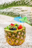 Tropical fruits salad in pineapple with cocktail umbrellas Royalty Free Stock Images
