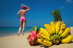 Tropical fruits and a woman in a bikini sunbathing on the beach on sea background. Royalty Free Stock Photography