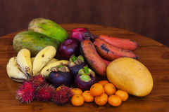 Tropical fruits on wooden table, close-up. Fresh juicy tropical fruits on wooden table and background, close-up Royalty Free Stock Photography