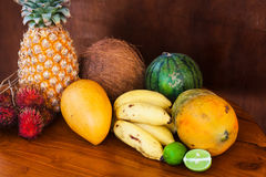 Tropical fruits on wooden table, close-up. Fresh juicy tropical fruits on wooden table and background, close-up Royalty Free Stock Photo