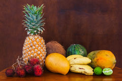 Tropical fruits on wooden table, close-up. Fresh juicy tropical fruits on wooden table and background, close-up Stock Images
