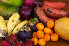 Tropical fruits on wooden table, top view. Fresh juicy tropical fruits on wooden table background, top view Royalty Free Stock Photography