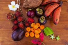 Tropical fruits on wooden table, top view. Fresh juicy tropical fruits on wooden table background, top view Royalty Free Stock Photos