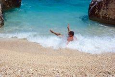 Tropical fun. A young man taking fun in a tropical sea Royalty Free Stock Photo