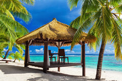 Tropical gazebo and two chairs on an island beach with palm tree Stock Photos