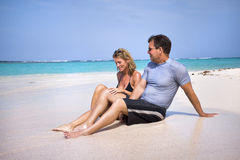 Tropical getaway. A couple sitting on a beautiful tropical beach shoreline Stock Photography