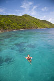 Tropical getaway. Young woman floating in crystal clear tropical water next to island Stock Images