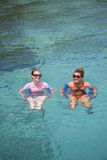 Tropical getaway. Two young women floating in clear tropical water Royalty Free Stock Image