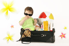 Tropical Getaway. Escape to the tropics. A baby sitting in a small suitcase packed with beachy things. Frangipani decorations can be removed if you like or stock photos