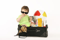 Tropical Getaway. Escape to the tropics. A baby sitting in a small suitcase packed with beachy things royalty free stock image
