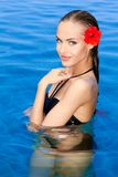 Tropical girl with flower on her ear. Posing in swimming pool royalty free stock image