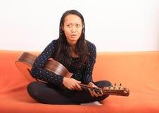 Tropical girl holding guitar Stock Photo