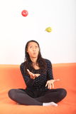 Tropical girl juggling with apple and pear Royalty Free Stock Images