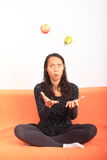 Tropical girl juggling with apple and pear Royalty Free Stock Photo