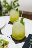 Tropical green cocktail lemonade with lemon, fresh mint and ice at outdoors cafe during the lunch in summer Stock Photography