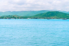 Tropical green hilly island shore and blue calm clean sea Stock Photo