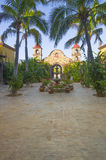 Tropical hacienda courtyard garden in Mexico. Nice mission style courtyard garden in mexican garden with bell towers, fountain, palm trees and tropical plants royalty free stock photo