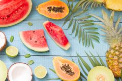 Tropical holiday summer abstract background with palms and fruits. On blue planks stock photo