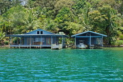 Tropical home and boat house over the sea Stock Images
