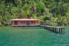 Tropical home over water with dock and lush shore Royalty Free Stock Photo