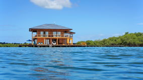 Tropical home over water viewed from sea surface Royalty Free Stock Photo