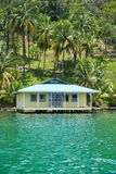 Tropical home on stilts over the sea Royalty Free Stock Photography