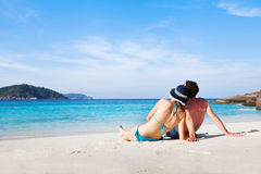 Tropical honeymoon. Couple sitting and relaxing on the paradise beach during their honeymoon Stock Images