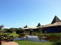 Tropical hotel complex. Lodges in tropical hotel complex with landscaped lake in foreground Royalty Free Stock Photography