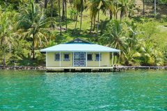Tropical house over the water viewed from the sea Stock Photo