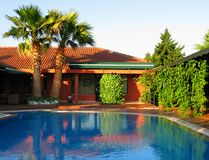 Tropical house with palms and swimming pool. Tropical house with swimming pool, little hotel Royalty Free Stock Photo