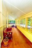 Tropical House Verandah. The beautiful rich coloured polished floors on a verandah of a colonial style house with yellow walls and window sills to match Royalty Free Stock Photo