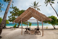 Tropical hut. An empty hut and a hammock on a tropical beach Royalty Free Stock Photography