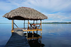 Tropical hut palapa over the water. Palapa hut over the water with thatched palm roof in a calm lagoon, Caribbean sea, Central America, Panama Stock Image