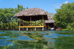 Tropical hut with thatch roof from water surface Stock Photo