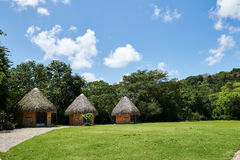Tropical huts on an island with conical thatch roofs, weaved out of coconut palm tree fronds. Bright daylight, blue sky with puffy. Cumulus clouds. Copy space Stock Images