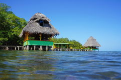 Tropical huts with thatched roof over the sea Royalty Free Stock Image